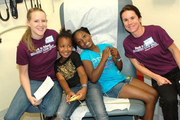 Two girls receive immunizations from CU students Katie Derington and Ania Sablik