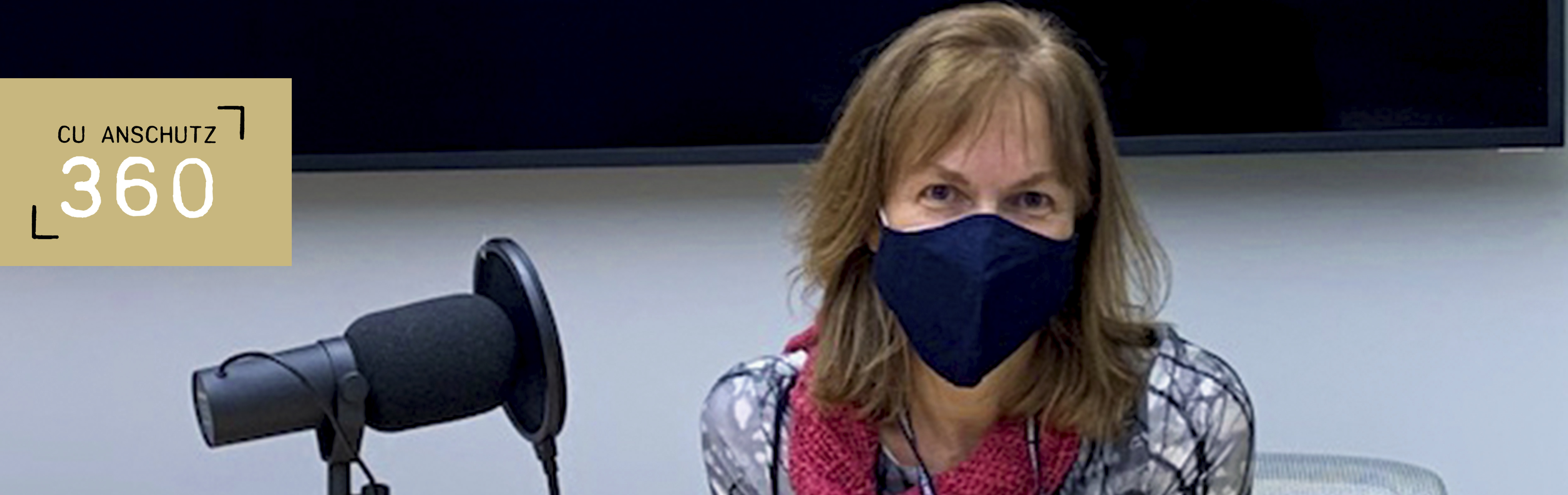 A masked Cathy Bradley sits next to a large podcast microphone