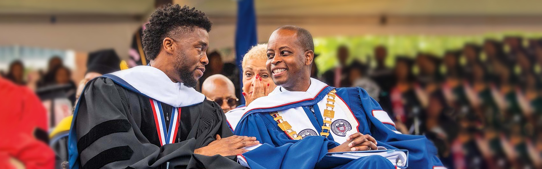 Chadwick Boseman talks to university president in graduation gown