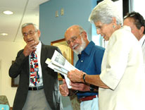 Carl Bartecchi, left, looks on as people at his reading room naming celebration flip through one of his books
