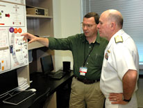 Navy Surgeon General Matthew Nathan, right, hears about bladder cancer research from Dr. Dan Theodorescu