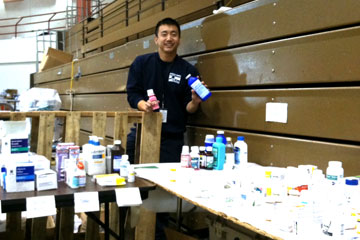 Stephen Lee, a Skaggs School of Pharmacy and Pharmaceutical Sciences student, displays medicine he distributed in New York