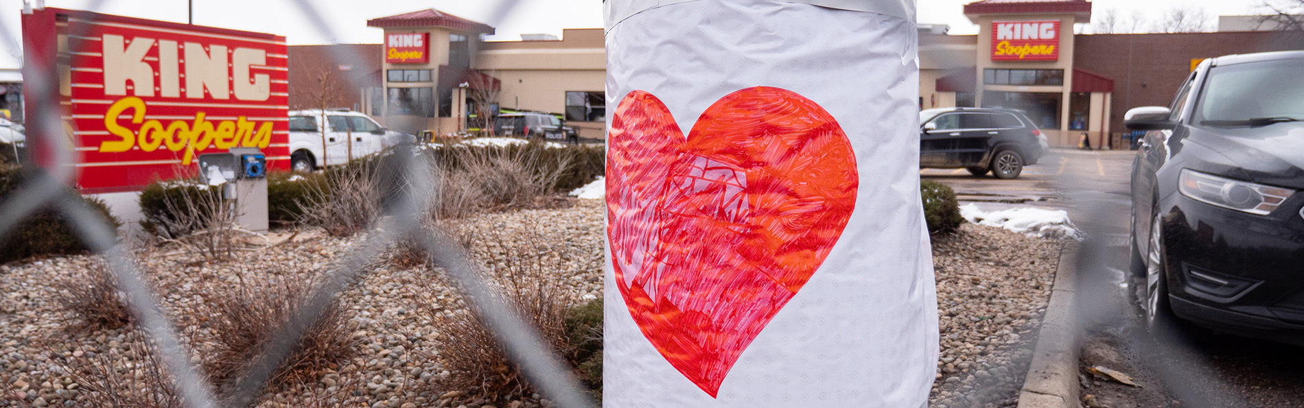 A large poster of a heart on a fence in front of Boulder King Soopers